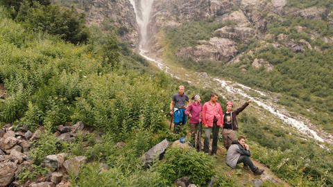 4k - Expedition of young tourists waving near mountain waterfall, aerial action Live Action