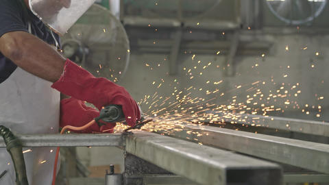 Slow motion of a worker using metal grinder with sparks flying at a metal shop Footage