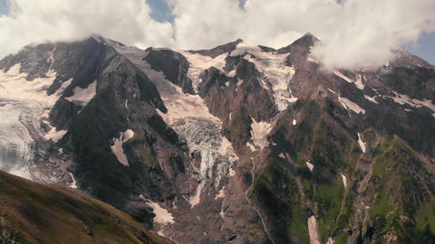 4k - Snow-capped peaks of mountains under the clouds in summer, aerial action Live Action