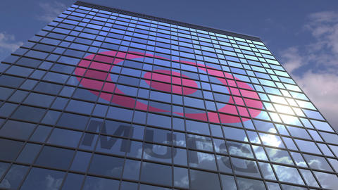 Logo of MITSUBISHI UFJ FINANCIAL GROUP on a media facade with reflecting cloudy Footage