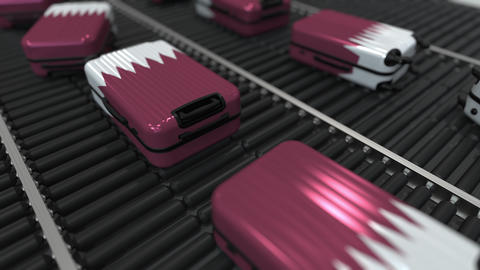 Many travel suitcases featuring flag of Qatar on roller conveyer. Qatari tourism Footage