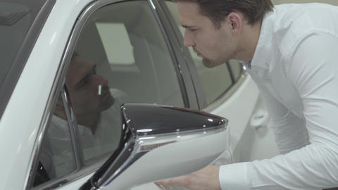 Portrait successful businessman inspects newly purchased auto from the car Live Action