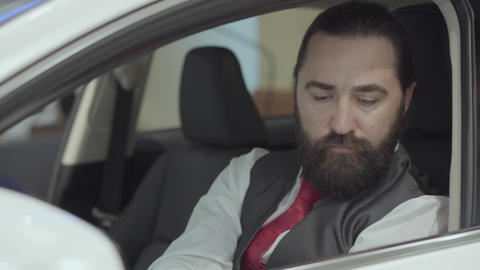Portrait attractive confident bearded man sitting in the vehicle and inspects Footage