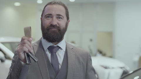 Portrait of a successful bearded business man in a business suit showing the key Footage