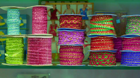 Rolls of fabric and textiles for sale stacked on shelves in shop Live Action