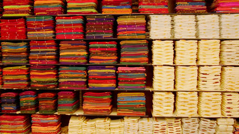 Textile shop in Indian clothing. Sari, traditional Indian dress. Shelves with fabrics of various Live Action