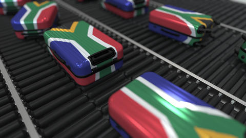 Many travel suitcases featuring flag of South Africa on roller conveyer. Tourism Live Action