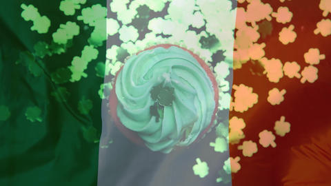 Shamrocks in paper falling on a muffin against an Irish flag Animation