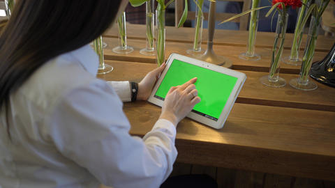 4K Woman Looking At Tablet Computer With Green Screen In Cafe Footage