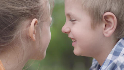Close-up face of adorable boy and girl sitting in the park, trying to rub their Live Action