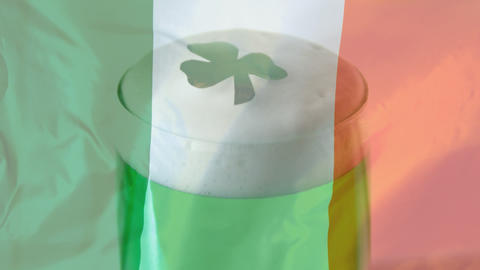 Shamrock falling on a green beer against an Irish flag background for St Patrick Day Animation