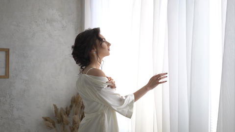 4K Beautiful Bride In A Dress Stands By The Window Dreaming Live Action
