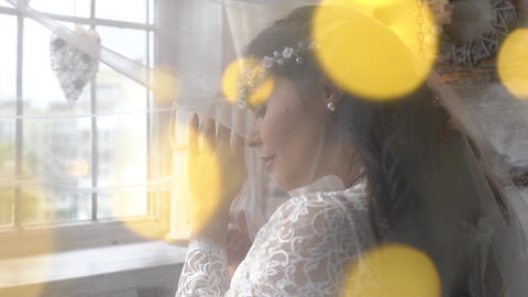 Beautiful Bride In A Dress Stands By The Window Dreaming, Smiling Charmingly Live Action