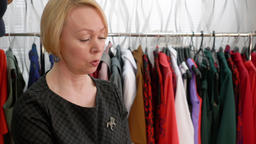 Cheerful senior woman trying accessories together consultant in fashion showroom Footage