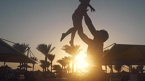 Dad throws up his daughter in the sky. happy childhood child with parents Live Action