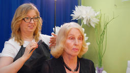 Hairstylist doing hairstyle for blond mature woman in beauty salon. Beauty Footage