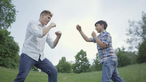 Young man and the boy boxing in the park. The young father imitating punches and Live Action