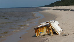 Old, rusty fridge on a beach. Environment pollution concept Live Action