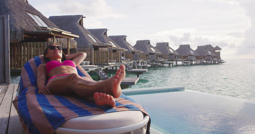 Travel vacation bikini woman relaxing lying down on lounge chair luxury resort Footage