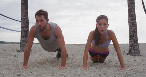Pushups fitness woman and man exercising push-ups on beach - Healthy living Footage