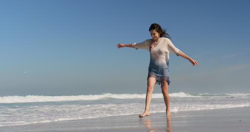 Young woman dancing on beach in the sunshine 4k Live Action