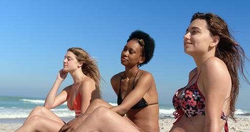 Young female friends sitting together at beach 4k Live Action