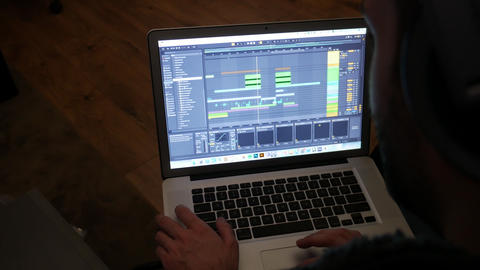 Musician creating a song from a laptop computer in home studio Live Action