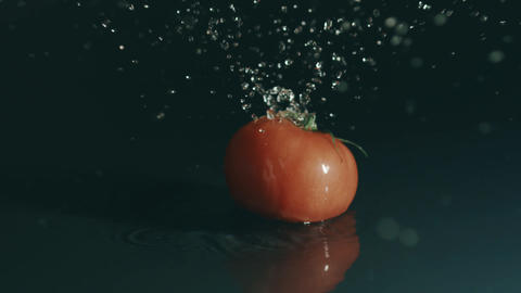 Single red tomato splashes in shallow water. Slow motion, close-up shot on Red Footage