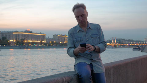 middle aged man uses mobile phone on embankment in dusk Footage