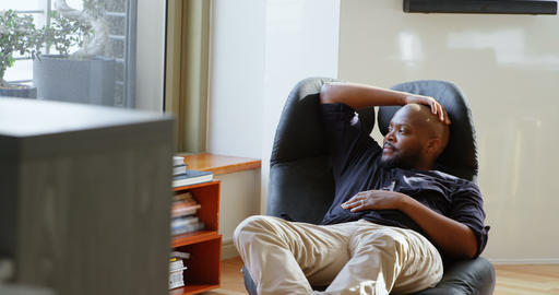 Man relaxing on chair in a comfortable home 4k Live Action