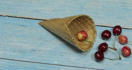 Berry ice cream. Berries of cherry in a waffle on a blue wooden background Live Action