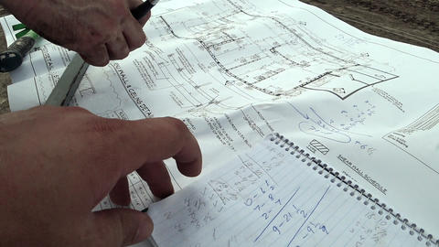 an architect and a construction engineer check the building plan of the building Live Action