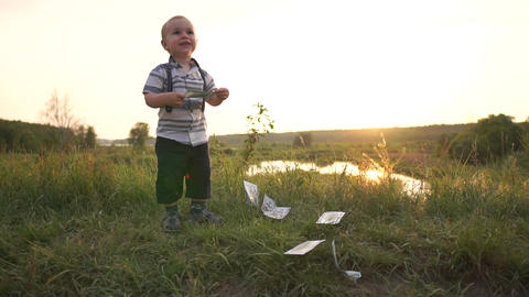 Small joyful child holds money banknote and throws it on the ground, slow motion Live Action