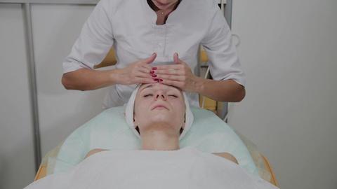 Beautiful woman doing facial massage at the beauty salon Footage