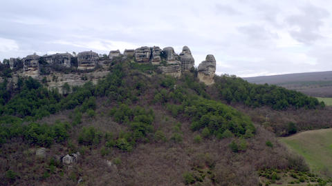 Medieval cave city fortress on mountain plateau at cliff. Fortress into rock Live Action