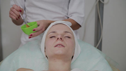 Professional cosmetologist puts a mask on the patient's face Footage