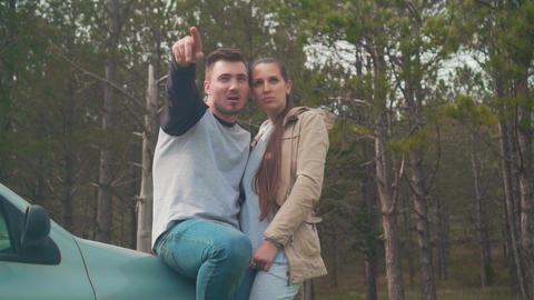 A guy and a girl are standing, leaning on a car in the forest. The guy shows the Live Action