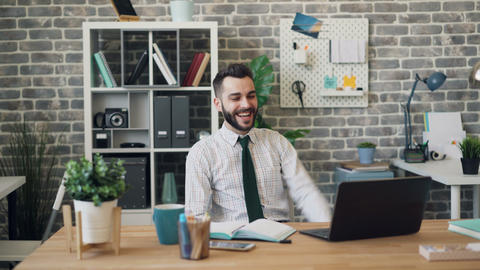 Happy employee using laptop then raising arms celebrating success in office Footage