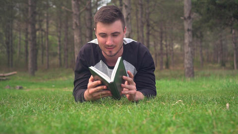 A young guy is lying on the green grass in the forest and reading a book. Rest Footage