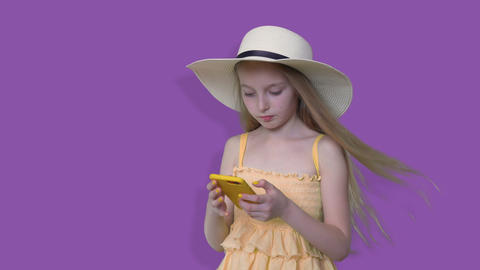Summer girl in hat looking mobile phone on violet background. Young girl Footage