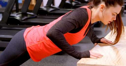 Determined beautiful Caucasian woman doing push-ups on wooden box 4k Live Action