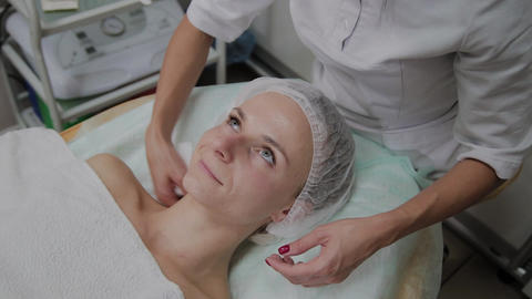 Professional beautician adjusts the patient's protective headgear Footage