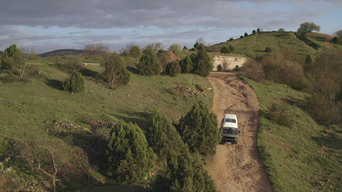 Car carefully goes down broken mountain dirt road. Lonely building on hill. Mountain landscape view. Live Action