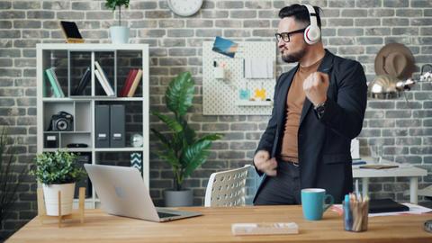 Cheerful entrepreneur having fun listening to music dancing wearing headphones Footage
