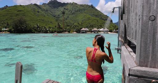 Luxury travel destination bikini woman taking an outdoor shower at resort hotel Live Action
