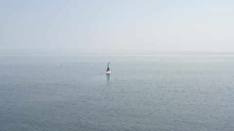 Rocky strip beach. Calm serene sea disappears behind horizon. Small ripples on the water. Misty Footage