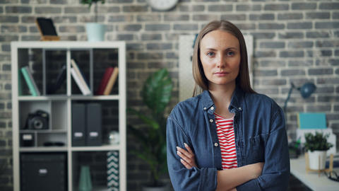 Portrait of good-looking young woman standing in office with arms crossed Live Action