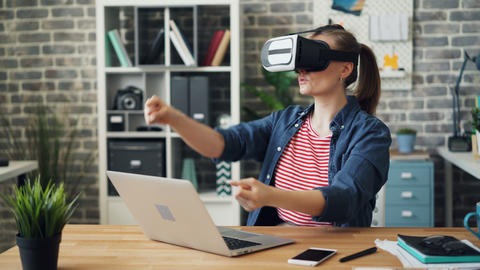 Girl having fun with virtual reality glasses moving arms driving in office Footage