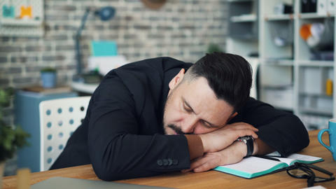Middle-aged brunet sleeping at work putting head on table sitting at desk alone Footage