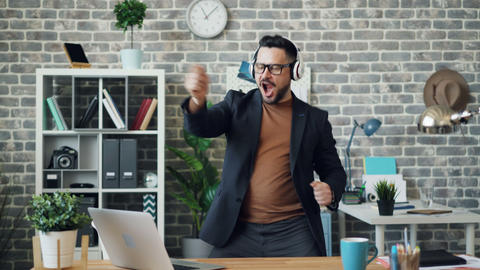 Funny businessman relaxing at work listening to music in headphones dancing Footage